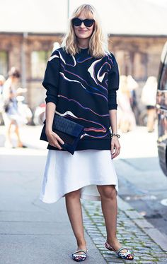 A printed sweater is worn with a high-low skirt, Mary-Jane flats, a clutch, and black sunglasses