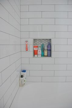 Choosing our shower tile design with subway tile and marble tile niche. This white and gray bathroom features IKEA vanities and herringbone floor.