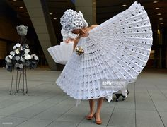A model displays a dress made from paper using the origami technique designed by Colombia designer Diana Gamboa, alongside metal objects produced by Gamboa's husband Luis Fernando Bohorquez during an art performance 'The Cyclops: a love story' in Tokyo on June 14, 2014. AFP PHOTO / Yoshikazu TSUNO