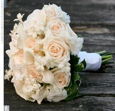 A hand-tied bouquet of cream roses, lisianthus, stephanotis, mini calla lilies, and white-edged ivy