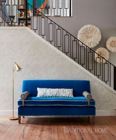 In the entry, CR Laine's blue armless sofa with fringe trim sits poised against the stairwell wall that's dressed in Thibaut's cream marbled wallcovering. - Photo: John Merkl / Design: Kim Scodro