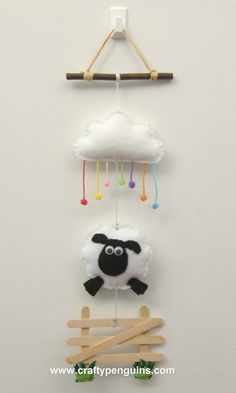 Decorative wall hanger, with sheep, gate and rainbow raindrop cloud, made from felt and lollipop sticks.