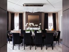 navy blue and brown | dining room decor | pinch pleat drapes | solid and sheer curtains | polished nickel bar rod | buttuned back velvet upholstered chairs | contemporary | home staging ideas white orchids | ceiling moulding | taupe traditional rug | fireplace