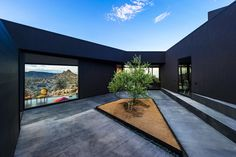 The house is built around a central courtyard, which is set to a backdrop of black walls, midnight quartz, high-gloss anthracite and darkene...