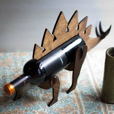 These are Wine-O-Saurs, handcrafted wooden wine bottle holders that look like dinosaurs. They come in Stegosaurus, Parasaur and Dimetrodon species and are the brainchild of Pete Betcher, who sells them in his Etsy store TheBackPackShoppe for $40 apiece (along with Triforce and Mario lamps).