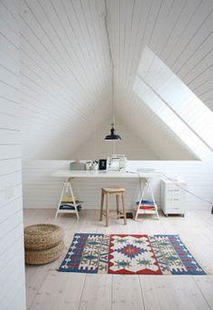白くペイントされた屋根裏材が広がり、パッと明るい屋根裏空間が生まれています。フロアをホワイトオークで揃えて、原色のアクセントカラーを敷物にプラスしています。