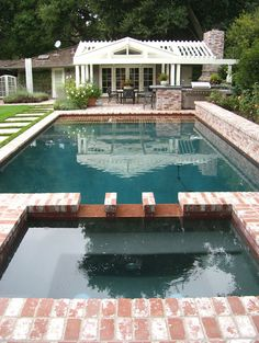 traditional pool with lovely used brick patio & decking