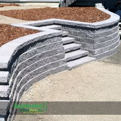 Grey concrete Versa-Lok retaining wall with steps added for easy movement throughout yard.
