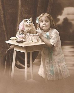 Girl in a lace dress, with her cat in a basket.
