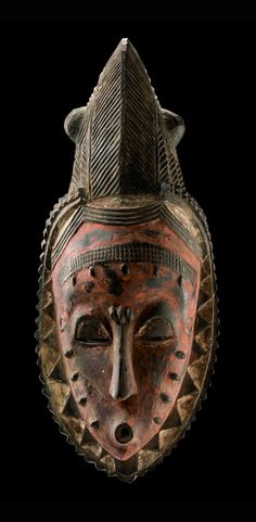 """Africa   Female face mask """"gu"""" from the Guro people of Ivory Coast   Wood; black patina, red pigment and kaolin"""