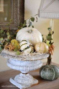 Green pumpkins and white pumpkins in metal urn