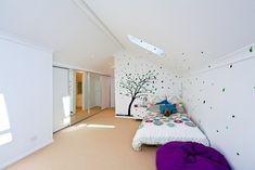 chambre sous combles avec un petit lit et déco murale arbre