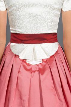 AlpenHerz Dirndl Jana mit weißem Mieder und rosé-farbenem Rock. Das verspielte Schößchen des Dirndl bietet einen bezaubernden Blickfang.