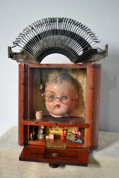 This piece is meant to hang on a wall. When mounted, a velvet ribbon hangs down the back of the box. When pulled, the stenographer's eyes close The Stenograper Found Object Art, Found Art, Recycled Art Projects, Bizarre, Creepy Dolls, Assemblage Art, Doll Head, Doll Parts, Box Art