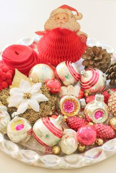 This dining room table centerpiece is really cool to me! Combining things like Vintage Christmas finds like the paper Santa, mercury Christmas Ornaments, & a couple of pine cones is brilliant!