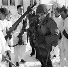 British and American soldiers inspect each other's weapons at the town of Champlon in Belgium. #WW2