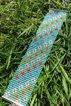 This lovely bracelet with colourful miniflowers on a rainbow frosted turquoise background was woven on a loom using Toho seed … Loom Bracelet Patterns, Bead Loom Bracelets, Bracelet Crafts, Bead Loom Patterns, Beading Patterns, Seed Bead Flowers, Beaded Flowers, Seed Bead Jewelry, Seed Beads