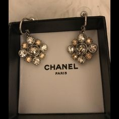 Authentic Chanel Crystal CC Logo Drop Earrings Authentic Chanel Crystal CC Logo Earrings with 4 clear crystals and 4 amber crystals surrounding 1 center large crystal with a silver CC logo in the middle. Jewelry Earrings