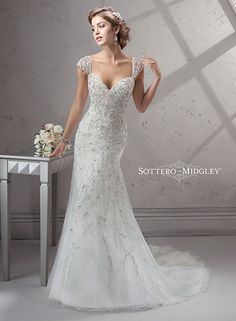 Stunning beaded A-line wedding gown, featuring twinkling Swarovski crystals and a plunging sweetheart neckline. Finished with corset closure to cinch the waist, and dazzling cap-sleeves.