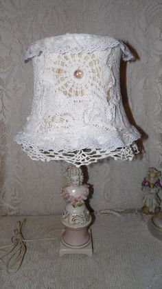 """Lampshades that are truly """"vintage from the 1920s"""" were not smothered in doily scraps.  Before the age of TV, people wanted maximum indoor lighting so they could use the hours before sleep productively.  Not a lamp from the 20s -- base and cord are post WWII.  The date is a fantasy Etsystory."""