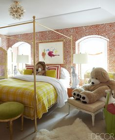 A niece's bedroom features a vintage bed, linens by Frette, and an ottoman by Oly; the light fixture is vintage, the print is by Helen Frankenthaler, the wallpaper is by Brunschwig & Fils, and the carpet is by Merida.   - ELLEDecor.com