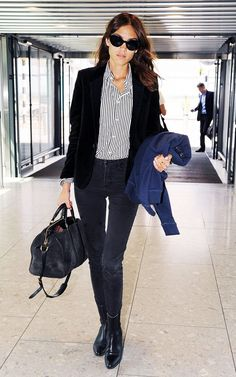 Alexa Chung pairs a crisp button-down shirt with black boots for a sleek travel look.