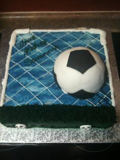 Soccer+Birthday+Cake+-+This+is+a+Birthday+cake+for+a+10+year+old+girl.+She+loves+soccer+and+wanted+a+soccer+cake+for+her+Birthday.+I+had+seen+other+photos+similar+to+this+one+on+Cake+Central+so+I+choose+to+make+one+like+it.+I+did+make+the+sky+in+the+background+look+a+little+more+realistic+however+by+mixingwhite+into+my+buttercream+after+it+had+been+tinted.+The+cake+is+yellow+with+Buttercream+frosting+and+the+ball+is+Rice+Krispie+treat+with+Fondant.