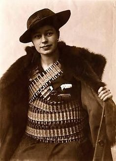"""One of the finest protectresses of the Helsinki White Guard. Miss E., a student at the University of Technology, bearing three bandoliers and a large pistol. Altogether Miss E. Is carrying some 1,350 bullets strapped to her person."""" First published with the above caption on the cover of the weekly magazine Suomen Kuvalehti on June 15th, 1918, by which time the Reds have lost the Civil War and Helsinki is already in the hands of the forces of the White faction..."""
