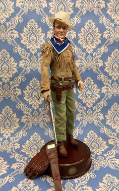 "The John Wayne Portrait Doll.  The Wayne family proudly presents a talking portrait doll honoring the ""Duke.""  A striking resemblance in hand-painted porcelain. Dressed in a re-creation of his costume from Hondo. With real leather shirt, gun belt, saddle bags, spurs and rifle. Touch the button on the hardwood base to hear the ""Duke"" speak in a recorded excerpt from the film. Limited Edition of 9500. Approximately 20"" (50.2 cm) in height, including base."