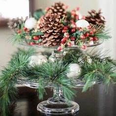 awesome centerpiece - stacked clear cake plates with evergreens, glass balls and red berries
