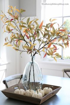 Simple farmhouse style fall centerpiece with branches and white pumpkins