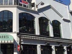 Brasserie Barbès. 124, boulevard de la Chapelle 75018 Paris. Métro Barbès.  Avec le cultissime Tati et ses néons brillants juste en face, le cinéma Louxor de l'autre côté du métro, le lieu se dresse comme avant, sur trois niveaux, désormais surplombés d'un rooftop. Au rez-de-chaussée, une grande brasserie avec terrasse, servant du petit-déjeuner (pas juste le croissant beurre) au dîner des classiques bistrot et de bons plateaux de fruits de mer.