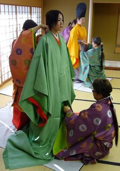 Women being dressed in junihitoe and kariginu layer by layer.