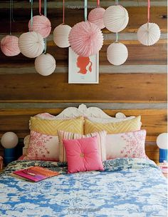 There's nothing about this kid's room that isn't great!n  Delightful mix of patterns. Awesome contrast between the crisply painted headboard & the rustic wood walls.  And lights (paper lanterns) en masse! They become a single design element instead of a bunch of tchotcke wimpy little lights. #rustic headboard