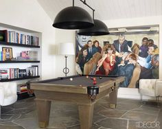 Flagstone flooring in the pool room, which features a painting by Arsen Roje, chairs from Blackman Cruz, and a light fixture by Hivemindesign; the pool table and metal floor lamp are custom made.