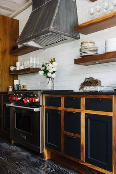 Industrial Kitchen Features A Plank Ceiling Lined With A Dark Steel Vent  Hood, Flanked By Stained Wood Floating Shelves, Placed Over A Small Wolf  Stove.