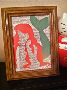 A homemade collage of Ariel (from Disney's The Little Mermaid) set to a literary background in an unique wooden frame