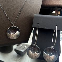 Sterling silver concave and convex surfaces are combined to create a serene mountain scene; complete with a starry sky. Earrings are approx....