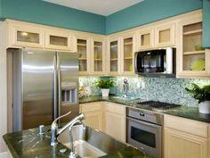 Küche mit Schränken aus hellem Holz und türkis wandfarbe auf dem oeberen Teil der Wand und Fliesen