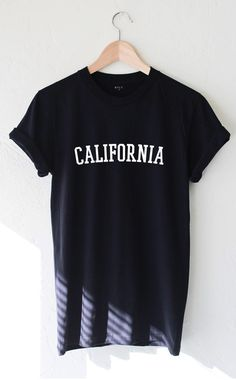 "- Description - Size Guide Details: Unisex & loose fit short sleeve tee in black with print featuring 'California' by NYCT Clothing. 100% Cotton. Made in USA. Sizing: 34"" / 86.36 cm width 27""/ 68.58 c"