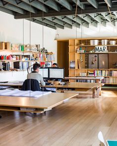 Open office plan with suspended work tables! Not sure how practicable this would be for the long term, but it maximizes floor space.wood floor exposed dark ceiling