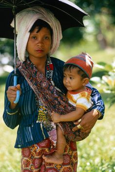 T'boli mother and son, Philippines  T'boli mother and son in the shade of an umbrella.      Eric Wheater Lonely Planet Photographer  © Copyright Lonely Planet Images 2011