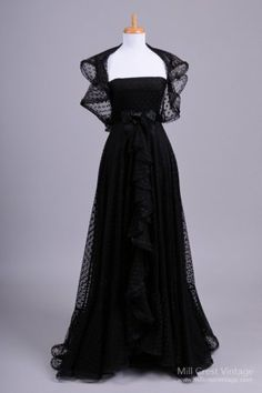 Early 1980's Polka Dot Tulle Formal Vintage Gown, designed by Richilene of New York.  The strapless bust features a flattering empire waist, which is separated from the skirt by an attached black satin sash ornamented with a bow.  Layers of flowing black polka dotted tulle form a skirt with a floor length front ruffle running down the front & all along the flared hem.  The under layer of the gown is a black satin; the bodice is fully lined & boned.  Tulle capelet flutters around the…