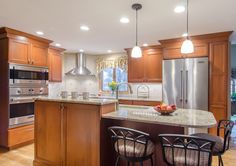 Transitional Kitchen - Stained cherry cabinetry, shaker style cabinetry, granite countertops, island seating, stainless steel appliances, sink in island.