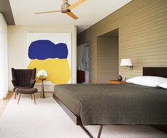 """""""The precision may make it look severe to some people,"""" says interior designer Thad Hayes, """"but the fabrics are tactile, and the house is made for comfort."""" The cedar paneling in the master bedroom of this rural Massachusettes home, as elsewhere in the house, reinforces the interior's relationship to the outdoors. The painting is Day and Night by Monique Prieto. Drapery fabric from Donghia.  Photo by Scott Frances, Architectural Digest, June 2007."""