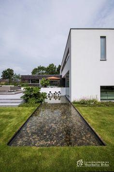 Aangelegde tuinen door tuinonderneming Monbaliu - Living terras met spiegelvijver aansluitend aan hedendaagse woning