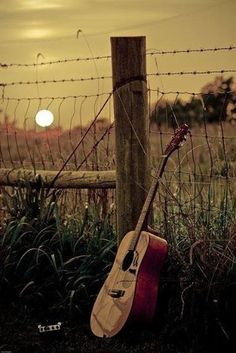 guitar against fence post