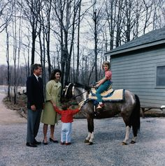 John F. Kennedy and Jackie Kennedy holding John Jr.'s hand, watch as Caroline Kennedy rides her pony, Macaroni. The saddle is a gift from King Hassan II of Morocco. March 31, 1963