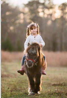 Little girl riding miniature pony