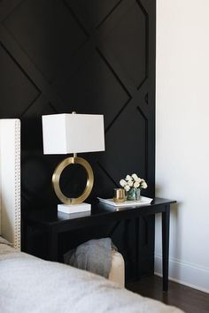 A gold ring lamp sits on a black console table placed in front of a black paneled accent wall beside a light gray linen wingback bed. - A gold ring lamp sits on a black console table placed in front of a black panele. Black Accent Walls, Black Walls, Black Accents, Wall Accents, Black Nightstand, Ring Lamp, Bedroom Black, Black White And Gold Bedroom, Black And White Office